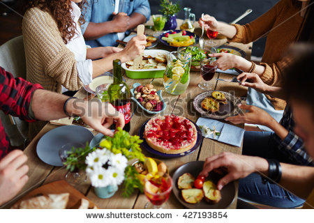 stock-photo-group-of-people-sitting-at-festive-table-and-eating-427193854
